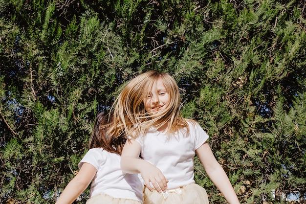 Niña sonriente saltando con un amigo