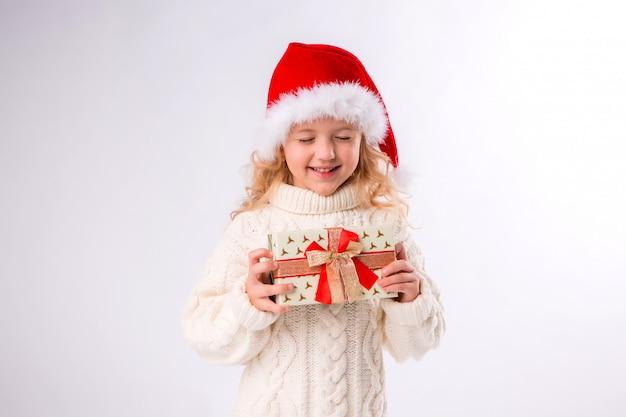 Niña sonriente en santa hat con caja de regalo sobre fondo blanco.