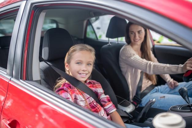 Niña sonriente sentada con asiento de pasajero, conduciendo con su mamá