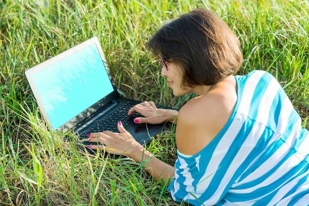 Niña sonriente sentada en el césped en un brillante día de verano y trabajando en la computadora
