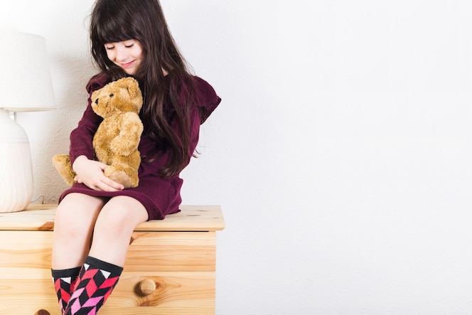 Niña sonriente sentada en la mesa con juguetes de peluche