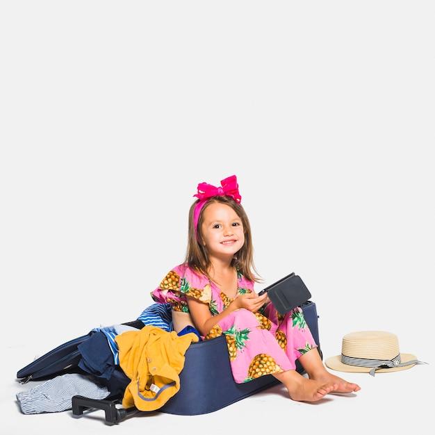 Niña sonriente sentada en maleta