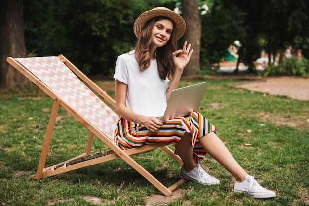Niña sonriente sentada con ordenador portátil en el parque al aire libre, mostrando ok