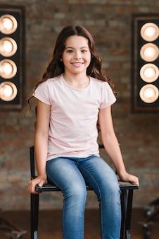 Niña sonriente sentada en la silla alta en el estudio