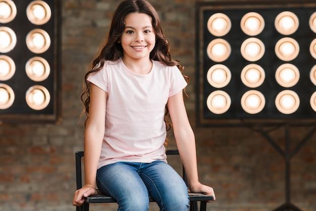 Niña sonriente sentada en la silla contra la pared de ladrillo con luces de escenario
