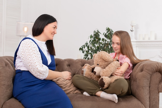 Niña sonriente sentada en un sofá junto a una doctora terapeuta sentada