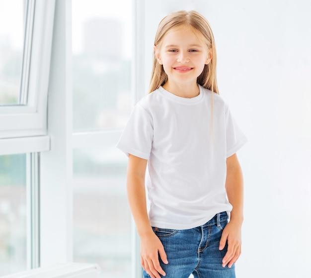 Niña sonriente en simple camiseta blanca en blanco