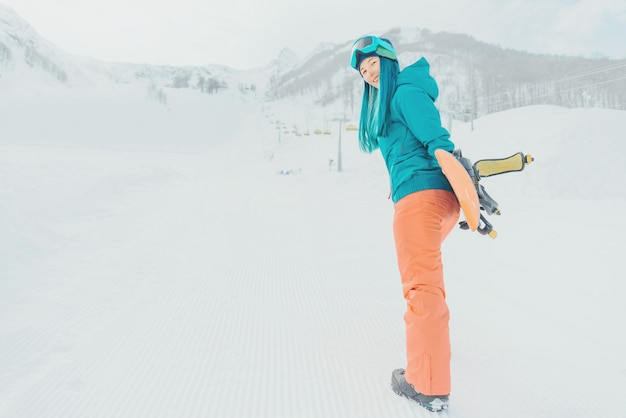 Niña sonriente con snowboard en la estación de esquí