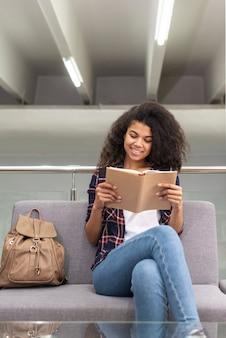 Niña sonriente en el sofá leyendo