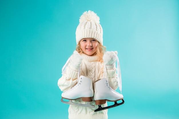 Niña sonriente en un sombrero blanco de invierno y suéter