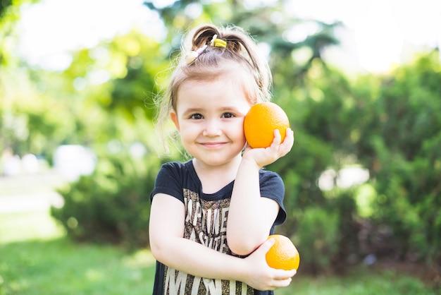 Niña sonriente sosteniendo dos naranjas frescas en el parque
