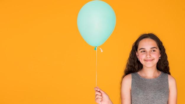 Niña sonriente sosteniendo un globo azul con espacio de copia