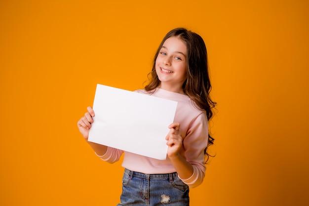 Niña sonriente sosteniendo una hoja en blanco sobre un fondo amarillo