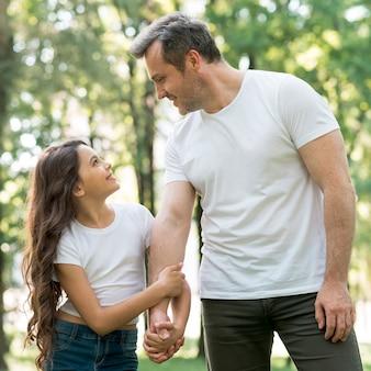 Niña sonriente sosteniendo la mano de su padre y mirándose