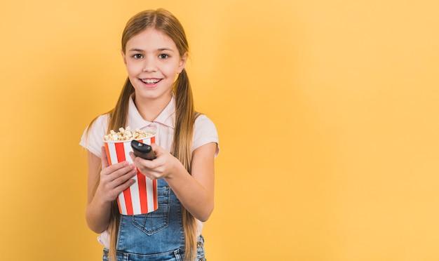 Niña sonriente sosteniendo palomitas de maíz en la mano cambiando el canal con control remoto sobre fondo amarillo