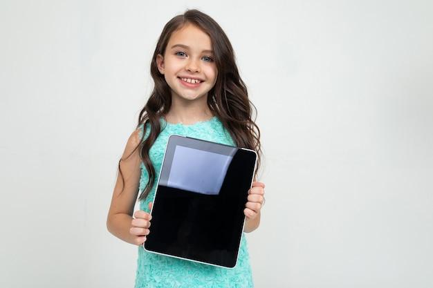 Niña sonriente sosteniendo una tableta con una plantilla para insertar una página web o publicidad sobre un fondo blanco
