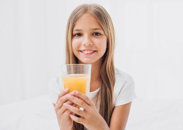 Niña sonriente sosteniendo un vaso de jugo de naranja