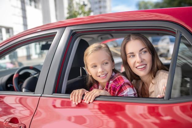Niña sonriente y su mamá mirando por la ventana en el asiento trasero del coche
