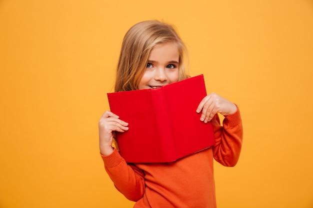 Niña sonriente en suéter escondiéndose detrás del libro y mirando a la cámara sobre naranja