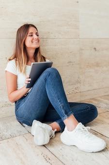Niña sonriente con tableta sentada en el suelo