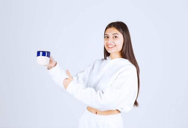 Niña sonriente con una taza y mostrando un pulgar hacia arriba sobre fondo blanco-gris.