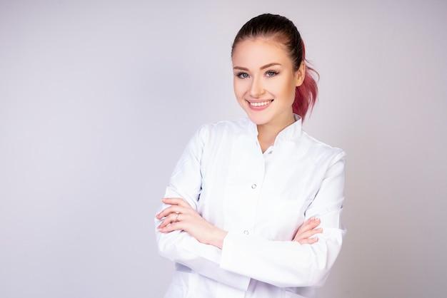Niña sonriente en uniforme médico blanco