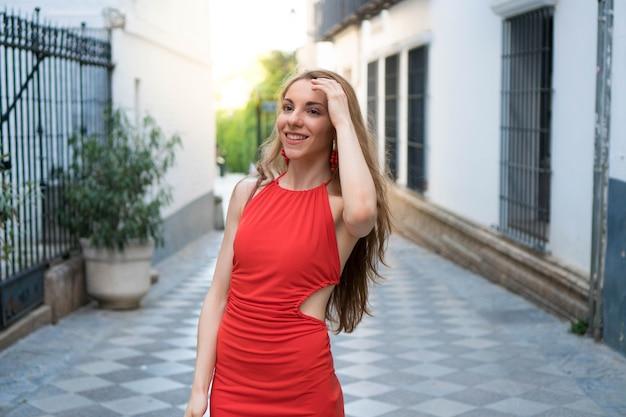 Una niña sonriente con un vestido rojo está haciendo turismo en una ciudad europea un turista elegantemente en españa