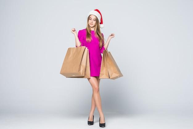 Niña sonriente en vestido rosa corto y sombrero de año nuevo de tacones sostienen bolsas de papel aisladas sobre fondo blanco.
