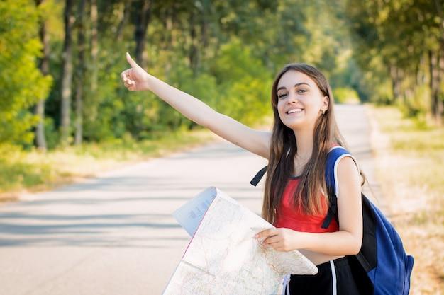 Niña sonriente viajando haciendo autostop levantando una mano intenta detener el coche