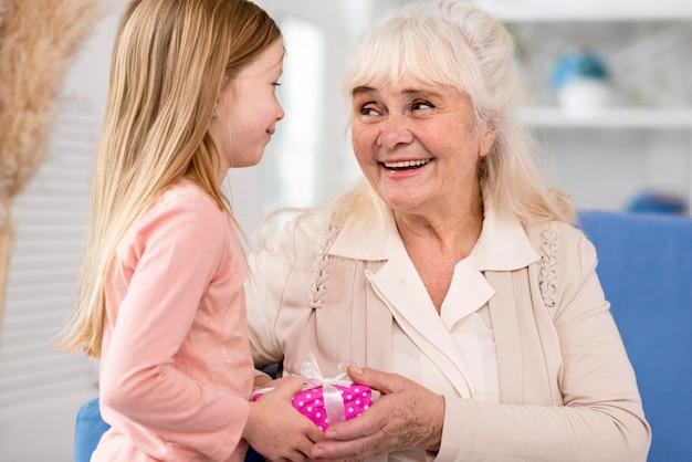 Niña sorprendente abuela con regalo