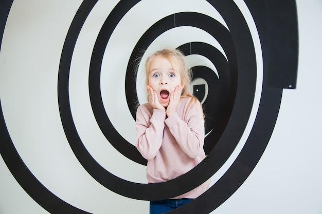 Niña sorprendida con cara emocional en espiral negro en el estudio.