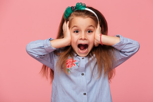 Niña sorprendida cubriendo sus oídos con ambas manos sin escuchar o escuchando gritos con la boca abierta