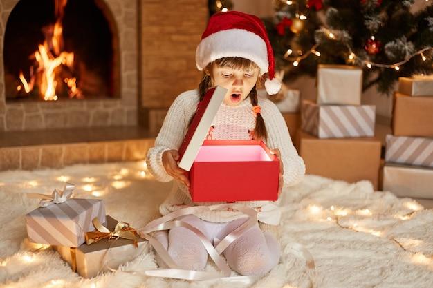Niña sorprendida extremadamente emocionada con suéter blanco y sombrero de santa claus, abre la caja de regalo con algo brillante, sentada en el piso cerca del árbol de navidad, cajas de regalo y chimenea.
