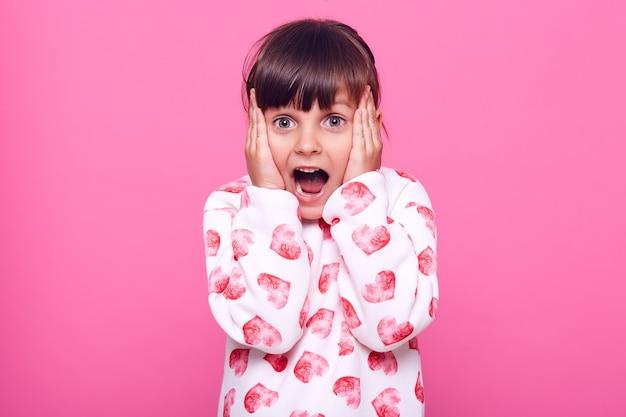 Niña sorprendida gritando apenas, mirando a la cámara con la boca abierta, manteniendo las manos en las mejillas, muy asustada, aislada sobre la pared rosa.