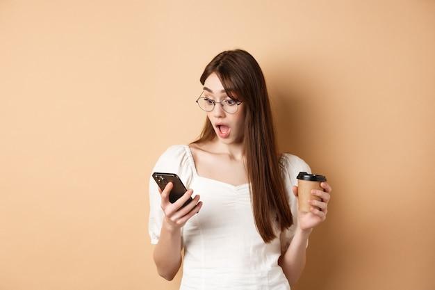 Niña sorprendida leyendo noticias emocionantes en el teléfono celular, con la mandíbula caída asombrada, de pie con la taza de café sobre fondo beige.