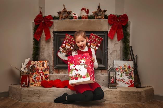 Niña sorprendida se regocija con el regalo de año nuevo en el fondo de la chimenea de navidad