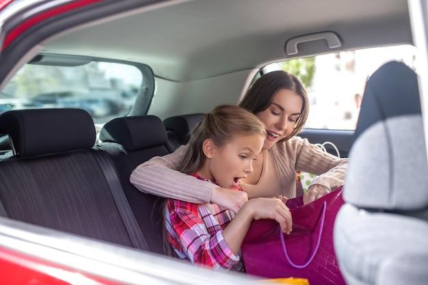 Niña sorprendida sentada en el asiento trasero con su mamá, mirando dentro de la bolsa de compras
