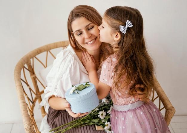 Niña sorprendiendo a su mamá con flores de primavera y regalo