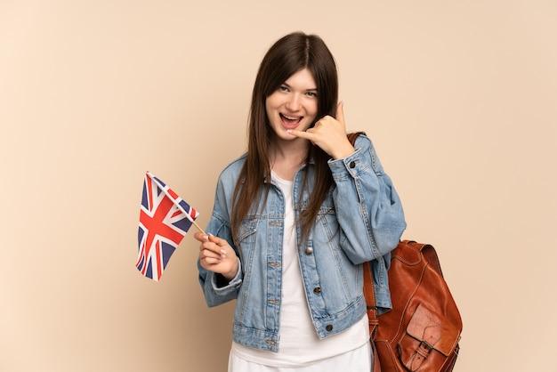Niña sosteniendo una bandera de reino unido aislada en beige haciendo gesto de teléfono