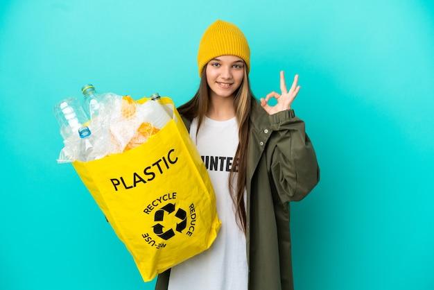 Niña sosteniendo una bolsa llena de botellas de plástico para reciclar sobre fondo azul aislado mostrando el signo de ok con los dedos