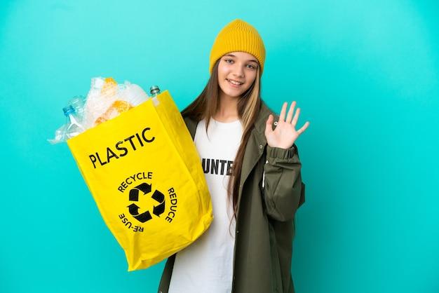 Niña sosteniendo una bolsa llena de botellas de plástico para reciclar sobre una superficie azul aislada saludando con la mano con expresión feliz