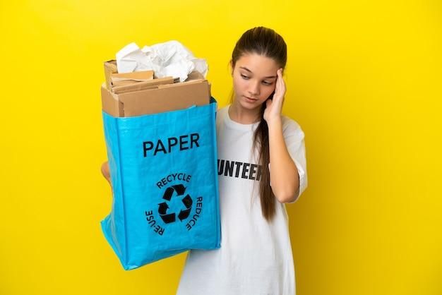 Niña sosteniendo una bolsa de reciclaje llena de papel para reciclar sobre fondo amarillo aislado con dolor de cabeza