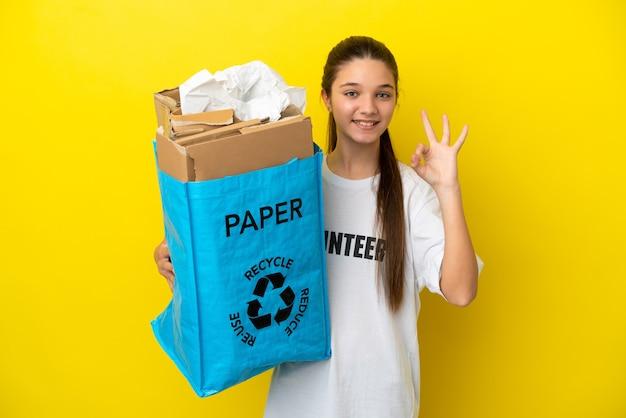 Niña sosteniendo una bolsa de reciclaje llena de papel para reciclar sobre fondo amarillo aislado mostrando el signo de ok con los dedos