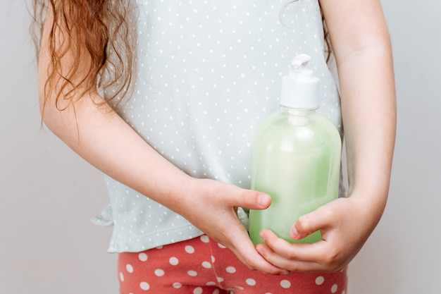 Niña sosteniendo una botella con jabón líquido