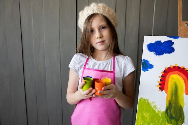 Una niña sosteniendo botellas de pintura de colores en la mano de pie cerca de la base