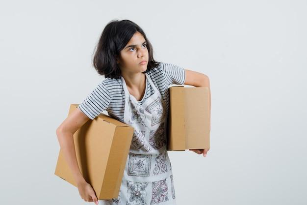 Niña sosteniendo cajas de cartón en camiseta, delantal y mirando vacilante,