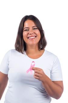 Niña sosteniendo la cinta del cáncer de mama sobre un fondo blanco sonriendo.
