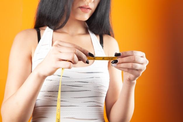 Niña sosteniendo una cinta métrica sobre un fondo naranja