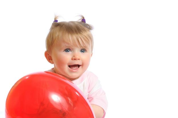 Niña sosteniendo globo rojo en las manos y sonriente, expresión de sorpresa en la cara. foto de bebé aislado sobre fondo blanco.