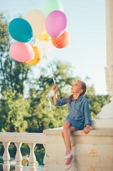 Niña sosteniendo globos de colores mirando hacia ellos